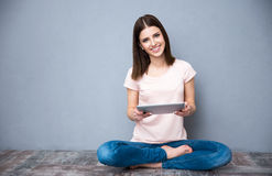 Mujer que se sienta en el piso con la tableta Fotos de archivo libres de regalías