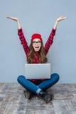 Mujer que se sienta en el piso con la tableta Imágenes de archivo libres de regalías