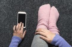 Mujer que se sienta en el piso con smartphone Foto de archivo