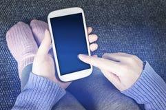 Mujer que se sienta en el piso con smartphone Fotografía de archivo libre de regalías