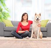 Mujer que se sienta en el piso con su perro casero imagen de archivo libre de regalías