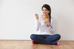 Mujer que se sienta en el piso que come el cuenco de fruta fresca imagen de archivo