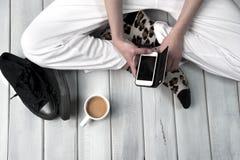 Mujer que se sienta en el piso que sostiene un smartphone Imagenes de archivo