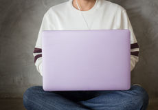 Mujer que se sienta en el piso usando el ordenador portátil Imagen de archivo