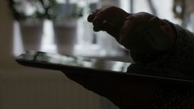 Mujer que se sienta en el piso y que usa la tableta vertical con la pantalla verde Ciérrese encima del tiro de las manos del ` s  almacen de metraje de vídeo