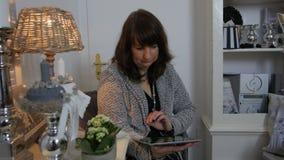 Mujer que se sienta en el piso y que usa la tableta vertical con la pantalla verde Ciérrese encima del tiro de las manos del ` s  almacen de video