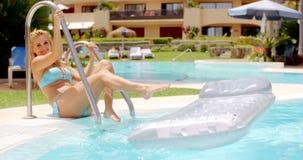 Mujer que se sienta en el Poolside con el colchón flotante almacen de metraje de vídeo