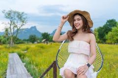 Mujer que se sienta en el puente de madera con el campo de flor amarillo del cosmos fotos de archivo