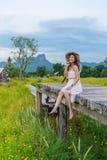 Mujer que se sienta en el puente de madera con el campo de flor amarillo del cosmos imagenes de archivo