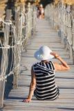 Mujer que se sienta en el puente en centro turístico de verano Imagenes de archivo