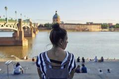 Mujer que se sienta en el río en Toulouse imágenes de archivo libres de regalías