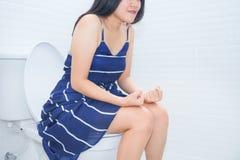Mujer que se sienta en el retrete con el puño de las manos - concepto del estreñimiento imagenes de archivo