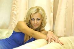 Mujer que se sienta en el sofá imagen de archivo