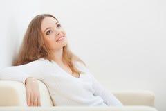 Mujer que se sienta en el sofá Fotos de archivo libres de regalías