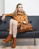 Mujer que se sienta en el sofá Foto de archivo libre de regalías