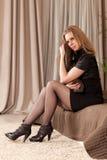 Mujer que se sienta en el sofá Fotos de archivo