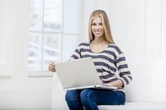 Mujer que se sienta en el sofá con el ordenador portátil Imagenes de archivo
