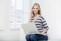 Mujer que se sienta en el sofá con el ordenador portátil Fotografía de archivo