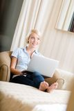 Mujer que se sienta en el sofá con el ordenador portátil Foto de archivo