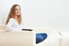 Mujer que se sienta en el sofá con el telecontrol Imagen de archivo libre de regalías