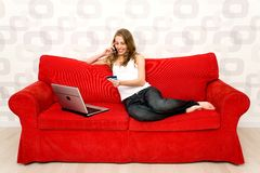 Mujer que se sienta en el sofá con la computadora portátil Imagenes de archivo