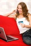 Mujer que se sienta en el sofá con la computadora portátil Fotos de archivo libres de regalías
