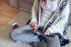 Mujer que se sienta en el sofá con la tableta y el café a disposición Fotografía de archivo