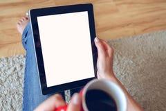Mujer que se sienta en el sofá con la tableta y el café a disposición Foto de archivo
