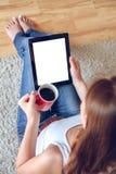Mujer que se sienta en el sofá con la tableta y el café a disposición Fotos de archivo libres de regalías