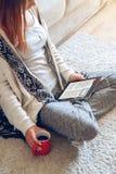 Mujer que se sienta en el sofá con la tableta y el café a disposición Imágenes de archivo libres de regalías