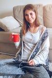 Mujer que se sienta en el sofá con la tableta y el café a disposición Fotos de archivo