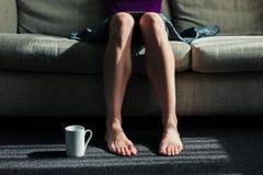 Mujer que se sienta en el sofá con la taza Imagen de archivo