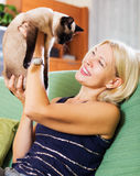 Mujer que se sienta en el sofá con su gato Imagen de archivo libre de regalías