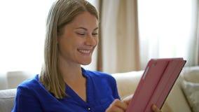 Mujer que se sienta en el sofá con su tableta Internet de la ojeada que sonríe, comunicando con sus amigos almacen de metraje de vídeo