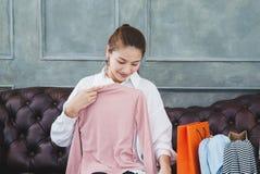 Mujer que se sienta en el sofá ella está sosteniendo una camisa rosada y está sonriendo imagen de archivo libre de regalías