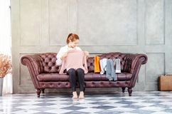 Mujer que se sienta en el sofá ella está sosteniendo una camisa rosada y está sonriendo foto de archivo libre de regalías