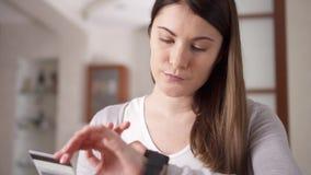 Mujer que se sienta en el sofá en la sala de estar que compra en línea con la tarjeta de crédito en el reloj elegante Compras en  almacen de metraje de vídeo