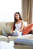 Mujer que se sienta en el sofá que sonríe con el ordenador portátil Imagenes de archivo
