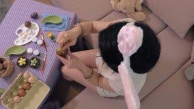 Mujer que se sienta en el sofá y el huevo de Pascua de pintura