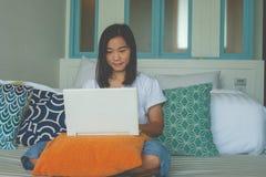 Mujer que se sienta en el sofá y que juega el ordenador portátil en el dormitorio imagen de archivo libre de regalías