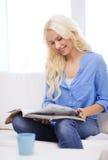 Mujer que se sienta en el sofá y que lee la revista Imagenes de archivo