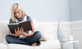 Mujer que se sienta en el sofá y que lee un libro Foto de archivo