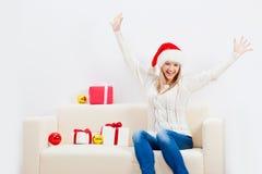 Mujer que se sienta en el sofá y que sostiene el regalo de los chrismtas Imágenes de archivo libres de regalías