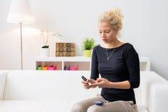 Mujer que se sienta en el sofá y que usa la aguja de la diabetes fotografía de archivo libre de regalías