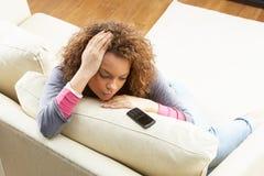 Mujer que se sienta en el sofá Wating para el teléfono móvil Foto de archivo