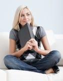 Mujer que se sienta en el sofá y que sostiene un libro Foto de archivo libre de regalías
