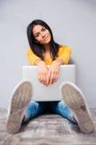 Mujer que se sienta en el suelo con la computadora portátil Imagen de archivo