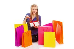 Mujer que se sienta en el suelo detrás de bolsos de compras Imagenes de archivo
