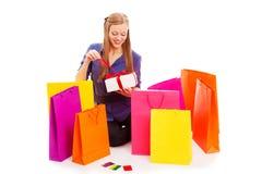 Mujer que se sienta en el suelo detrás de bolsos de compras Foto de archivo