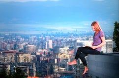 Mujer que se sienta en el tejado y el libro de lectura Fotografía de archivo